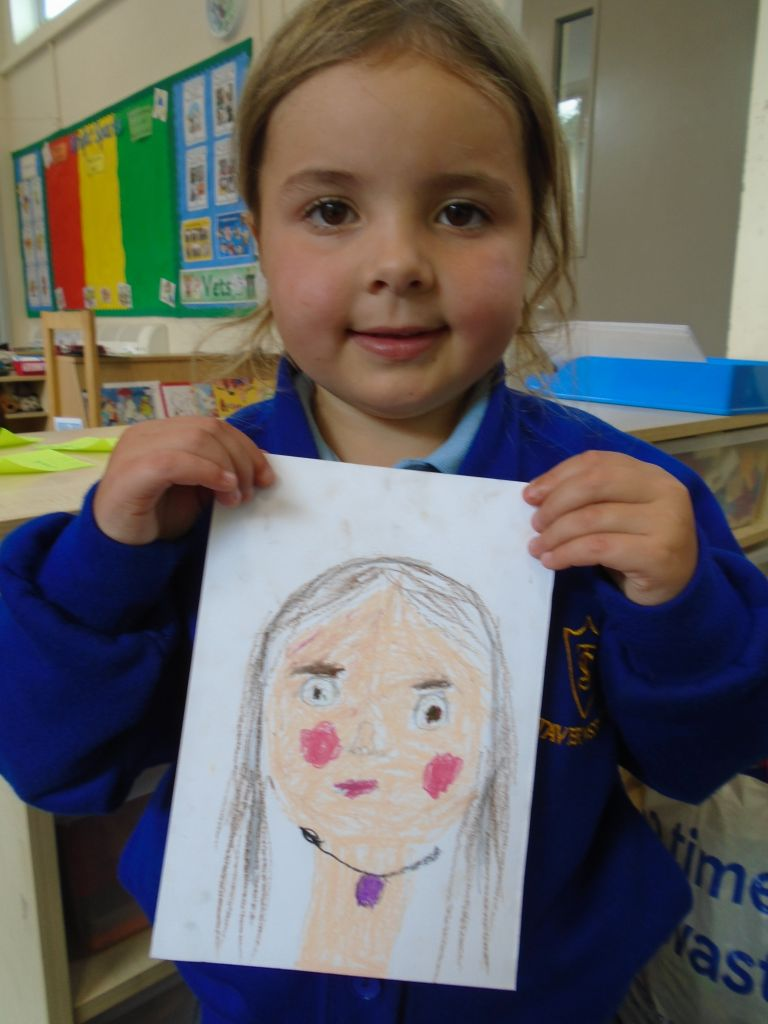 Child holding a portrait drawing